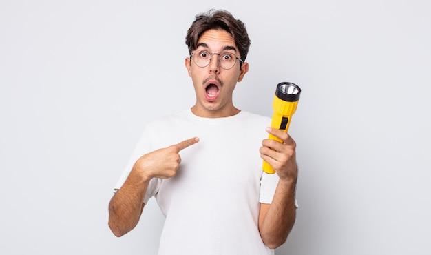 Jonge spaanse man die geschokt en verrast kijkt met wijd open mond, wijzend naar zichzelf. lantaarn concept