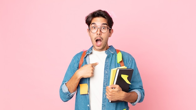 Jonge spaanse man die geschokt en verrast kijkt met wijd open mond, wijzend naar zichzelf. studentenconcept
