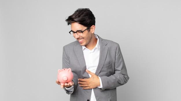 Jonge spaanse man die hardop lacht om een hilarische grap en een spaarvarken vasthoudt