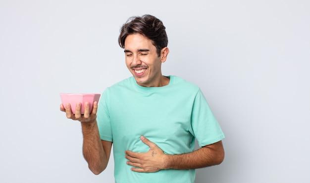 Jonge spaanse man die hardop lacht om een hilarische grap. lege kom concept