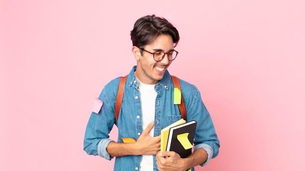 Jonge spaanse man die hardop lacht om een hilarische grap. studentenconcept