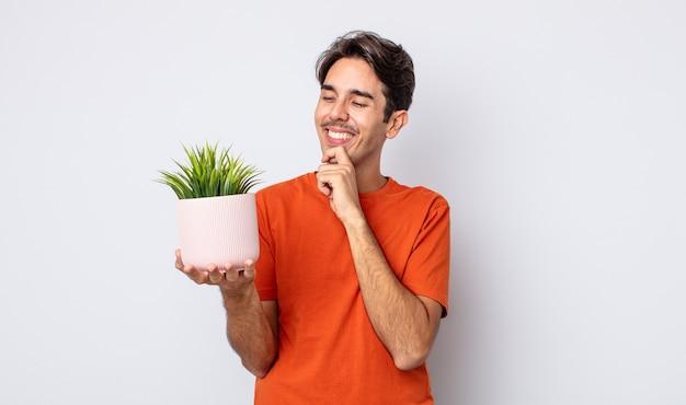 Jonge spaanse man die lacht met een gelukkige, zelfverzekerde uitdrukking met de hand op de kin. decoratief plantenconcept