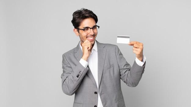 Jonge spaanse man die lacht met een gelukkige, zelfverzekerde uitdrukking met de hand op de kin en een creditcard vasthoudt Premium Foto