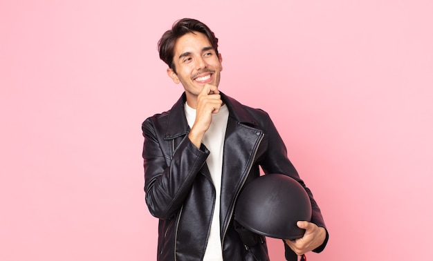 Jonge spaanse man die lacht met een gelukkige, zelfverzekerde uitdrukking met de hand op de kin. motorrijder concept