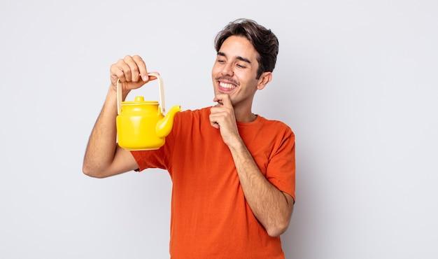 Jonge spaanse man die lacht met een gelukkige, zelfverzekerde uitdrukking met de hand op de kin. theepot concept