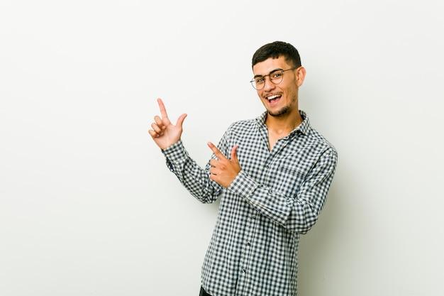 Jonge spaanse man die met wijsvingers een copyspace richt, opwinding en verlangen uitdrukt.