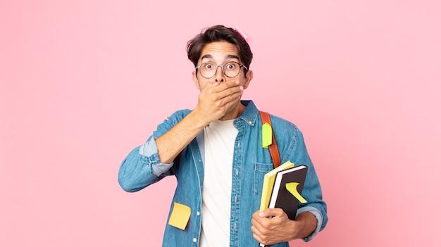 Jonge spaanse man die mond bedekt met handen met een geschokt. studentenconcept