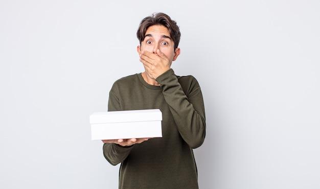 Jonge spaanse man die mond bedekt met handen met een geschokt. witte doos concept
