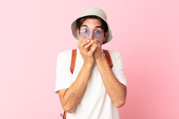 Jonge spaanse man die mond bedekt met handen met een geschokt. zomer concept