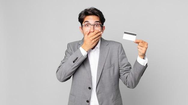 Jonge spaanse man die mond bedekt met handen met een geschokte en een creditcard vasthoudt