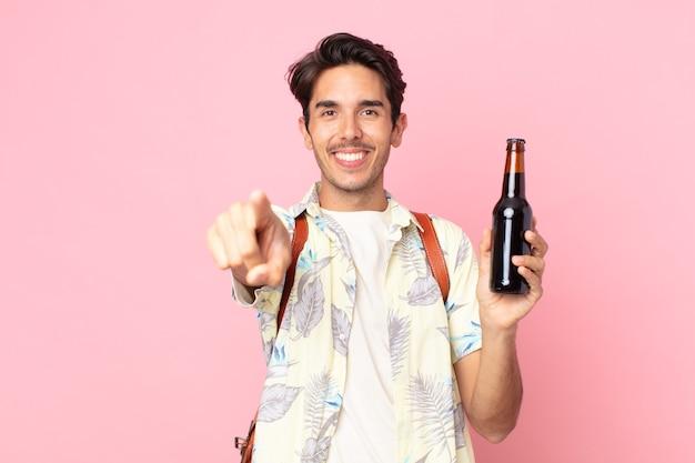 Jonge spaanse man die naar de camera wijst en jou kiest en een flesje bier vasthoudt