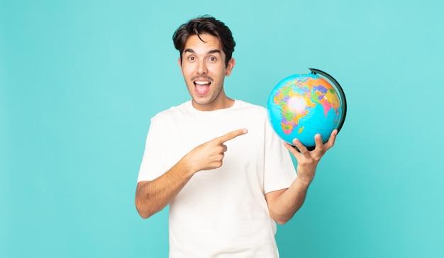 Jonge spaanse man die opgewonden en verrast kijkt en naar de zijkant wijst en een wereldbolkaart vasthoudt