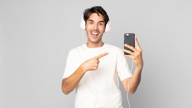 Jonge spaanse man die opgewonden en verrast kijkt en naar de zijkant wijst met een koptelefoon en smartphone