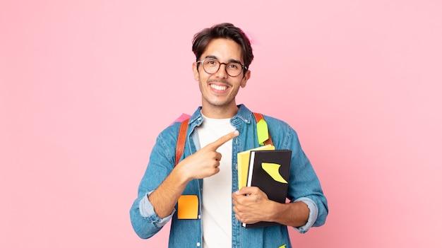 Jonge spaanse man die opgewonden en verrast kijkt en naar de zijkant wijst. studentenconcept