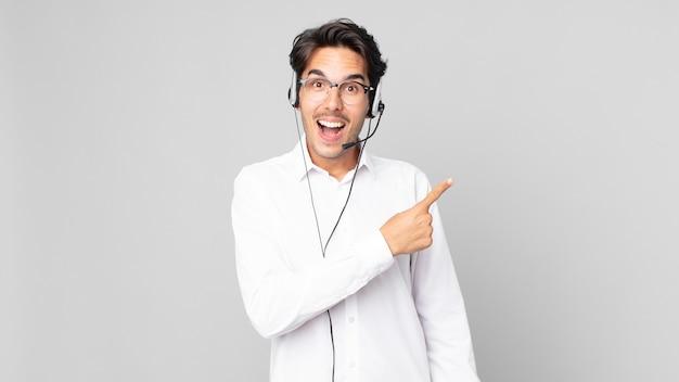 Jonge spaanse man die opgewonden en verrast kijkt en naar de zijkant wijst. telemarketeer concept