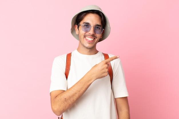 Jonge spaanse man die opgewonden en verrast kijkt en naar de zijkant wijst. zomer concept
