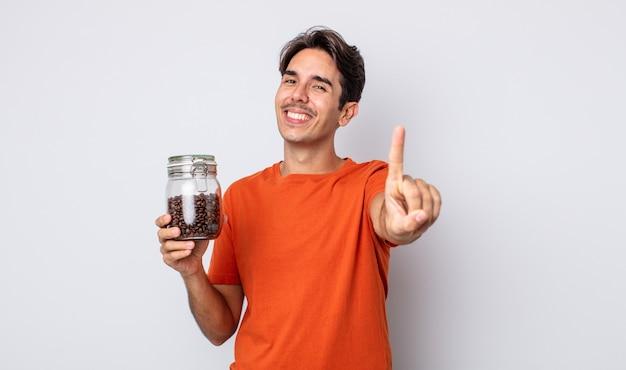 Jonge spaanse man die trots en vol vertrouwen glimlacht en nummer één maakt. koffiebonen concept
