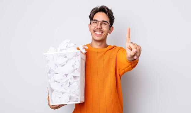 Jonge spaanse man die trots en vol vertrouwen glimlacht en nummer één maakt. papier ballen prullenbak concept