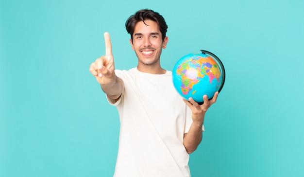 Jonge spaanse man die trots en zelfverzekerd glimlacht en nummer één maakt en een wereldbolkaart vasthoudt