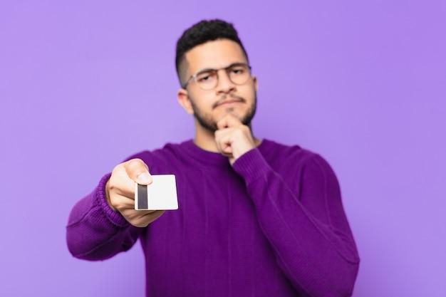 Jonge spaanse man die twijfelt of een onzekere uitdrukking heeft en een creditcard vasthoudt