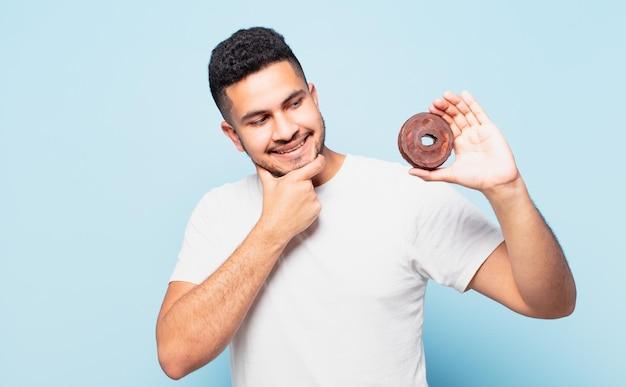 Jonge spaanse man die uitdrukking denkt en een donut vasthoudt