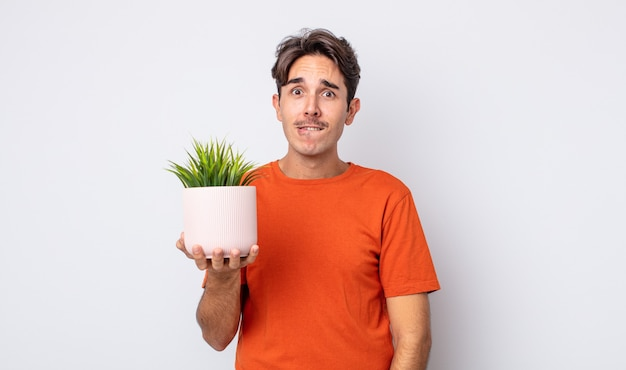 Jonge spaanse man die verbaasd en verward kijkt. decoratief plantenconcept