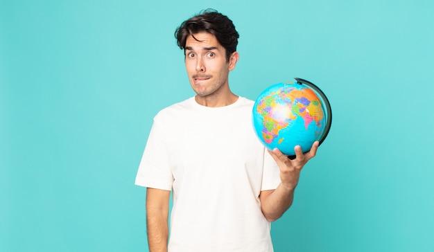 Jonge spaanse man die verbaasd en verward kijkt en een wereldbolkaart vasthoudt