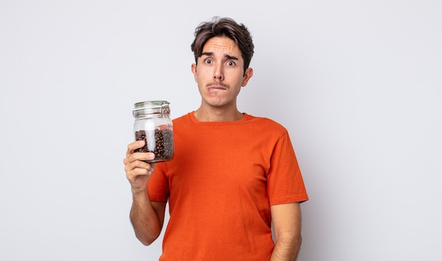Jonge spaanse man die verbaasd en verward kijkt. koffiebonen concept