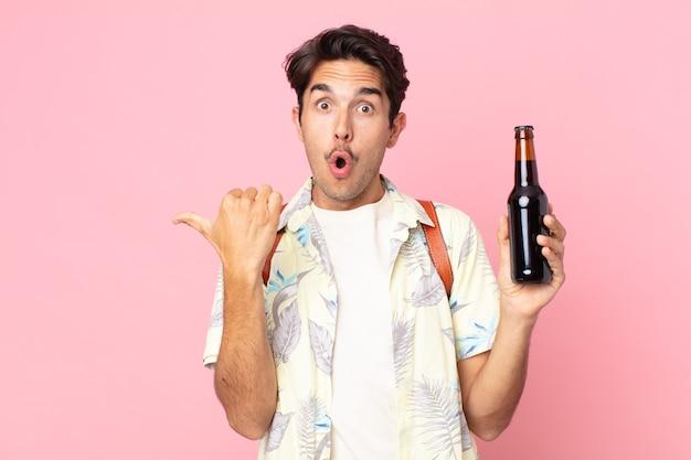 Jonge spaanse man die verbaasd kijkt in ongeloof en een flesje bier vasthoudt