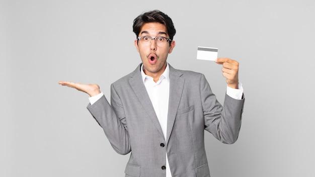 Jonge spaanse man die verrast en geschokt kijkt, met open mond terwijl hij een object vasthoudt en een creditcard vasthoudt