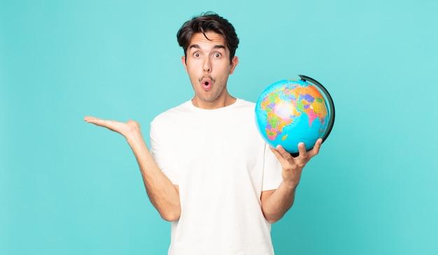 Jonge spaanse man die verrast en geschokt kijkt, met open mond terwijl hij een object vasthoudt en een wereldbolkaart vasthoudt