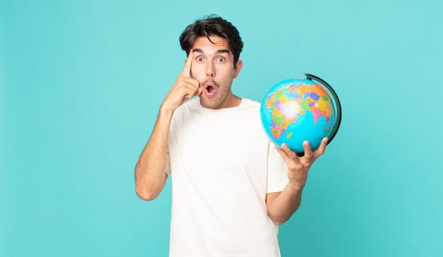 Jonge spaanse man die verrast kijkt, een nieuwe gedachte, idee of concept realiseert en een wereldbolkaart vasthoudt