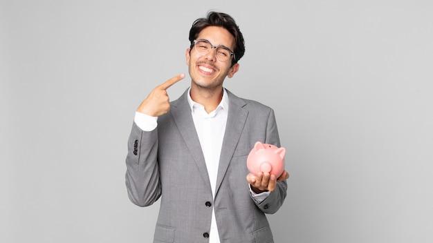 Jonge spaanse man die vol vertrouwen glimlacht, wijst naar zijn eigen brede glimlach en een spaarvarken vasthoudt