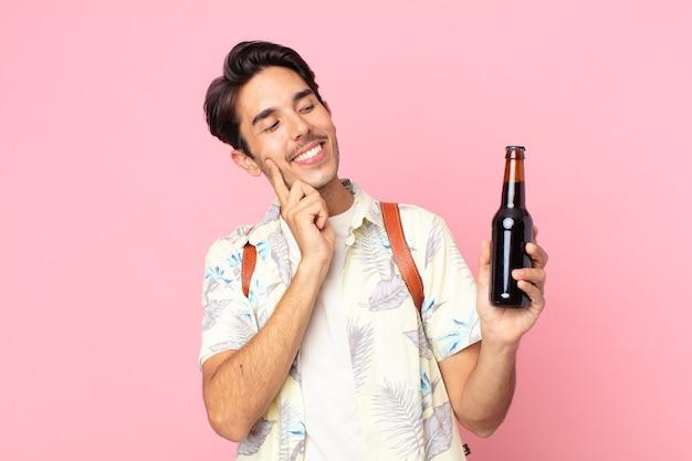 Jonge spaanse man die vrolijk lacht en dagdroomt of twijfelt en een flesje bier vasthoudt