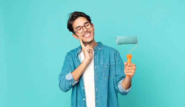 Jonge spaanse man die vrolijk lacht en dagdroomt of twijfelt en een verfroller vasthoudt