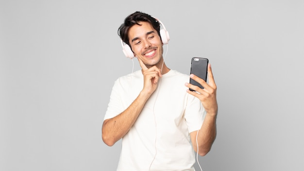 Jonge spaanse man die vrolijk lacht en dagdroomt of twijfelt met koptelefoon en smartphone