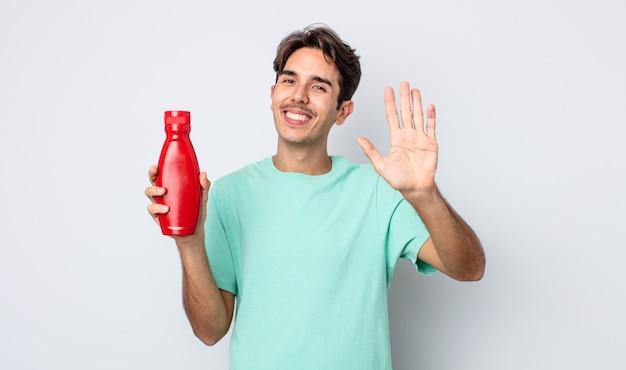 Jonge spaanse man die vrolijk lacht, met de hand zwaait, je verwelkomt en begroet. ketchup-concept