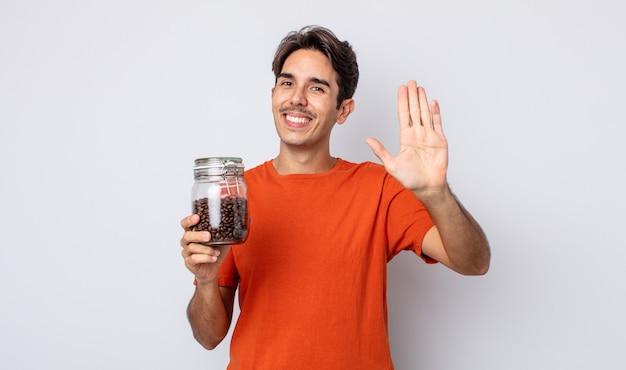 Jonge spaanse man die vrolijk lacht, met de hand zwaait, je verwelkomt en begroet. koffiebonen concept