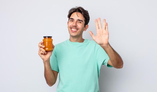 Jonge spaanse man die vrolijk lacht, met de hand zwaait, je verwelkomt en begroet. perzik gelei concept