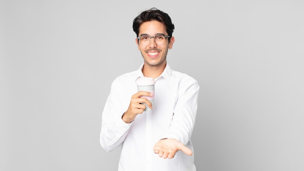 Jonge spaanse man die vrolijk lacht met vriendelijk en een concept aanbiedt en toont en een afhaalkoffie houdt