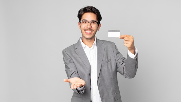 Jonge spaanse man die vrolijk lacht met vriendelijk en een concept aanbiedt en toont en een creditcard vasthoudt