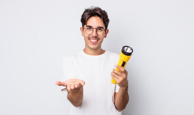 Jonge spaanse man die vrolijk lacht met vriendelijk en een concept aanbiedt en toont. lantaarn concept