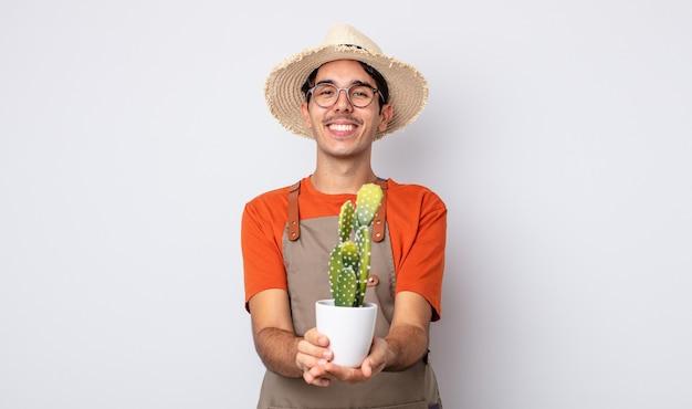 Jonge spaanse man die vrolijk lacht met vriendelijk en een concept aanbiedt en toont. tuinman met cactusconcept