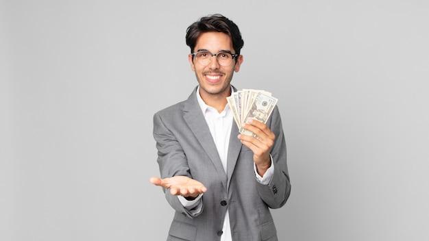 Jonge spaanse man die vrolijk lacht met vriendelijk en een concept aanbiedt en toont