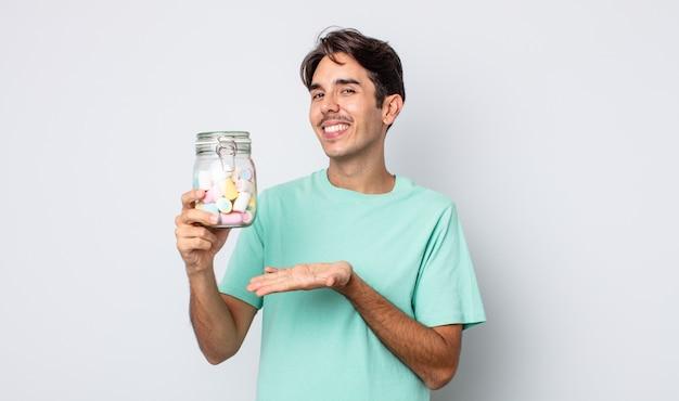 Jonge spaanse man die vrolijk lacht, zich gelukkig voelt en een concept toont. gelei snoepjes concept