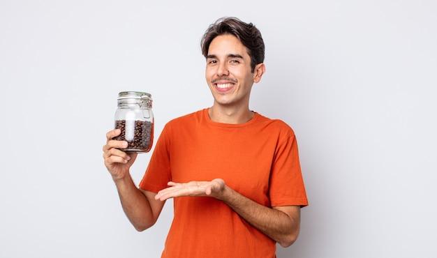 Jonge spaanse man die vrolijk lacht, zich gelukkig voelt en een concept toont. koffiebonen concept