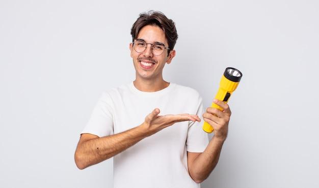 Jonge spaanse man die vrolijk lacht, zich gelukkig voelt en een concept toont. lantaarn concept