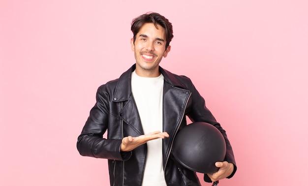Jonge spaanse man die vrolijk lacht, zich gelukkig voelt en een concept toont. motorrijder concept