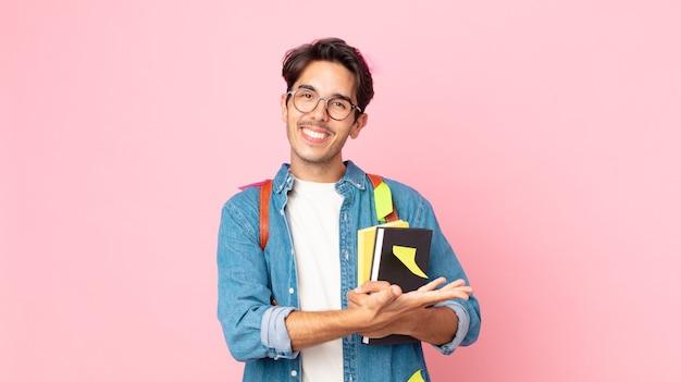 Jonge spaanse man die vrolijk lacht, zich gelukkig voelt en een concept toont. studentenconcept