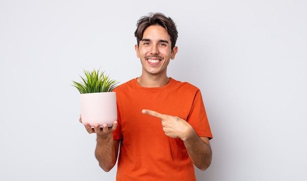 Jonge spaanse man die vrolijk lacht, zich gelukkig voelt en naar de zijkant wijst. decoratief plantenconcept